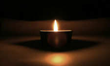 Solitary candle with reflections in the darkness