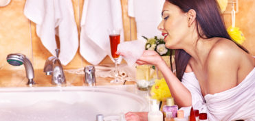 Woman applying moisturizer at bathroom.